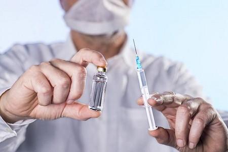Баночка с лекарством и шприц в руках врача