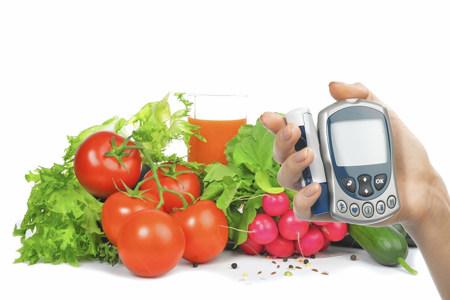 Глюкометр в руке и овощи