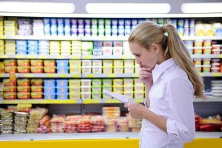 женщина задумалась возле витрины с продуктами