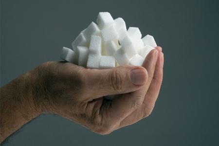 Рука держит кубики сахара